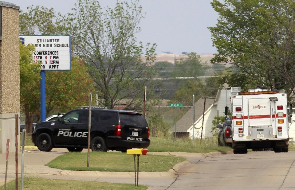 Police and fire vehicles are parked outside Stillwater Junior High School in Stillwater, Okla., Wednesday, Sept. 26, 2012. A 13-year-old student shot and killed himself in a hallway at an Oklahoma junior high school before classes began Wednesday, police said,   (AP Photo/Sue Ogrocki)