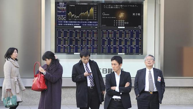 People stand by an electronic stock board of a securities firm in Tokyo, Friday, Dec. 26, 2014. Shares were mostly higher in quiet trading Friday in Asia, as most markets in the region and across the globe were closed for Christmas holidays. China's Shanghai Composite Index extended gains in the second day of a rebound from this week's earlier sell-off. Japan's Nikkei 225 stock index edged 10.21 points or 0.06 percent higher and closed at 17,818.96 for the week. (AP Photo/Koji Sasahara)