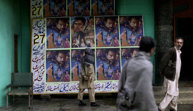In this Sunday, April 29, 2012 photo, a Pakistani man looks at a board displayed on it advertisements of a local movie, outside Taj Mahal cinema in Abbottabad, Pakistan. One year since U.S. commandos