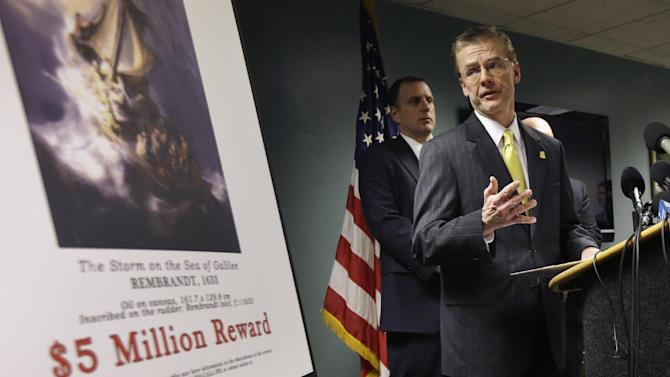 Federal Bureau of Investigation (FBI) Special Agent in Charge Richard DesLauriers, right, stands next to a poster that shows a Rembrandt painting and a reward while facing reporters during a news conference at FBI headquarters in Boston, Monday, March 18, 2013. The FBI believes it knows the identities of the thieves who stole art valued at up to $500 million from Boston's Isabella Stewart Gardner Museum more than two decades ago. DesLauriers says the thieves belong to a criminal organization based in New England and the mid-Atlantic states. (AP Photo/Steven Senne)