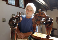 In this Thursday, Sept. 18, 2012 photo, Tony Dow, actor, director and artist, poses with, from left, Two Figures and Struggle, at his home and studio in the Topanga area of Los Angeles. When it comes time to sitting down in a studio and carving out bronze and wooden sculptures inspired by the nature all around him, Wally isn&#39;t leaving it up to the Beav these days. Dow, who famously played the Beaver&#39;s older brother Wally on the classic 1950s-60s sitcom &quot;Leave it To Beaver,&quot; is carving out a name for himself in the art world these days, as an abstract artist. (AP Photo/Reed Saxon)