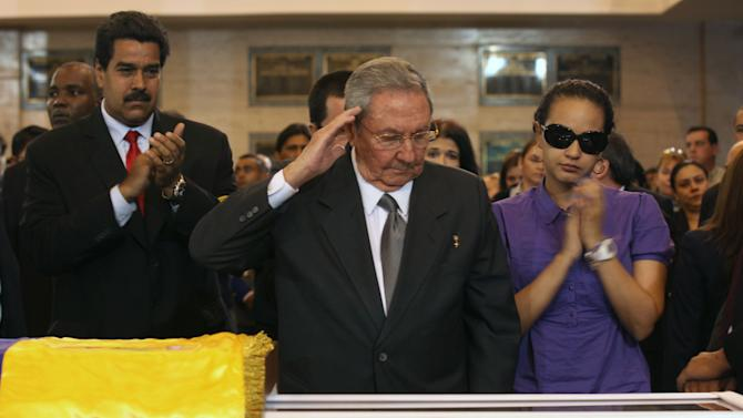 In this photo released by Miraflores Press Office,  Cuba's President Raul Castro salutes as he stands next to the coffin containing the remains of  Venezuela's late President Hugo Chavez during his wake at a military academy where his body will lie in state until his funeral in in state in Caracas, Venezuela, Thursday, March 7, 2013.  Nicolas Maduro, Venezuela's acting president, said Chavez's  remains will be put on permanent display at the Museum of the Revolution, close to the presidential palace where Chavez ruled for 14 years. A state funeral for Chavez attended by some 33 heads of government is scheduled to begin Friday morning.  At right is Chavez's daughter Rosa Virginia Chavez and left is Vice-President Nicolas Maduro.(AP Photo/Miraflores Press Office)