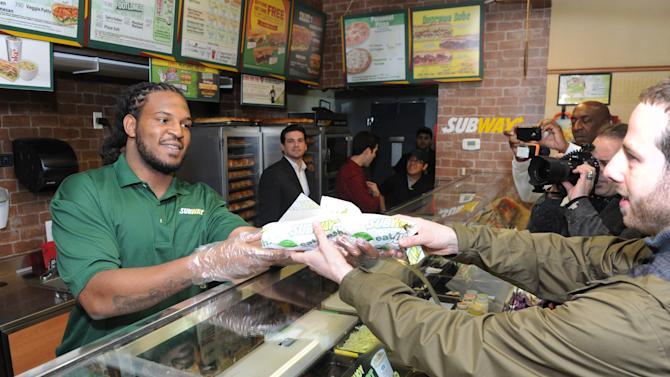 "IMAGE DISTRIBUTED FOR SUBWAY -Linebacker Jarvis Jones, 2013 draft prospect and newest Famous Fan of SUBWAY, serves up a sandwich after unveiling a life-size ""Smokehouse BBQ Chicken"" sculpture to announce his official SUBWAY Famous Fan title, Tuesday, April 23, 2013, in New York.  The sculpture is an artistic representation of the football star from the chest up, standing approximately three feet tall and made of almost entirely SUBWAY Smokehouse BBQ Chicken.  Jarvis joins a roster of fellow Famous Fans that include Robert Griffin III, Justin Tuck, Michael Strahan, Blake Griffin and Michael Phelps.† (Photo by Diane Bondareff/Invision for SUBWAY/AP Images)"