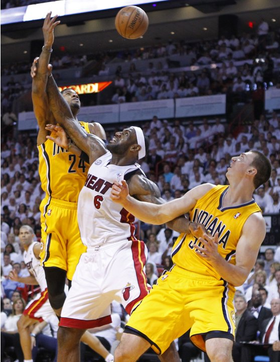 Miami Heat's James fights for a rebound with Indiana Pacers' George and Hansbrough during their NBA Eastern Conference final basketball playoff in MiamI