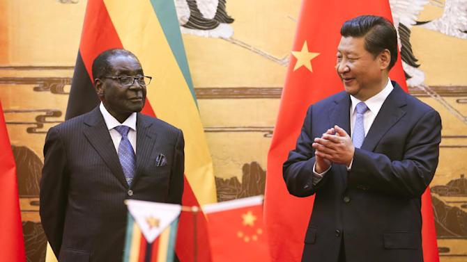 Zimbabwean President Robert Mugabe, left, looks on as his Chinese counterpart Xi Jinping applauds during a signing ceremony at the Great Hall of the People in Beijing, China, Monday, Aug. 25, 2014. Mugabe met with Xi on a visit to China hoping the long-time ally and economic giant can help the African nation's ailing economy. (AP Photo/Diego Azubel, Pool)