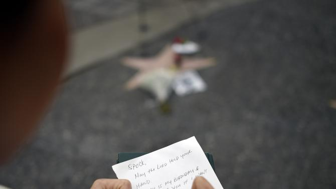 Christine Nguyen Chiem writes a sympathy note to place on the Hollywood Walk of Fame star of actor Leonard Nimoy, which is adorned with flowers on Hollywood Boulevard in Los Angeles, California