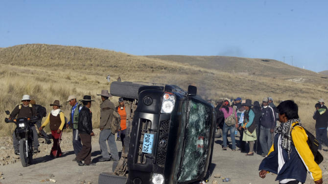 People surround a flipped a car during a protest at the Tinaya copper mine owned by Swiss-based Xstrata plc in Espinar, Peru, Monday, May 28, 2012. Peru's government declared a 30-day state of emergency in Espinar, a Peruvian highland province, on Monday after it said two people were killed and dozens of police officers injured in violent anti-mining protests. (AP Photo/Gerardo Luna)