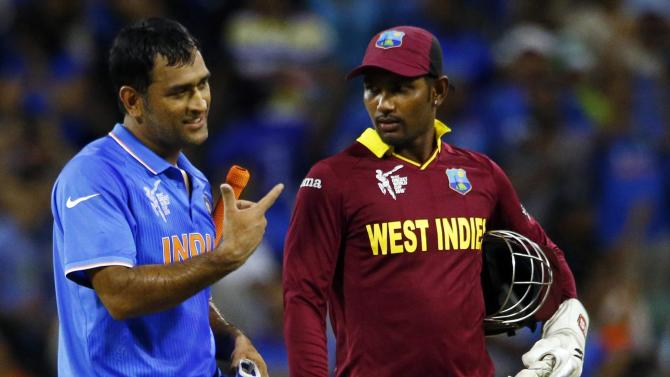 India's captain MS Dhoni walks with West Indies' wicket keeper Denesh Ramdin off the field together following India's four wicket victory at the Cricket World Cup in Perth