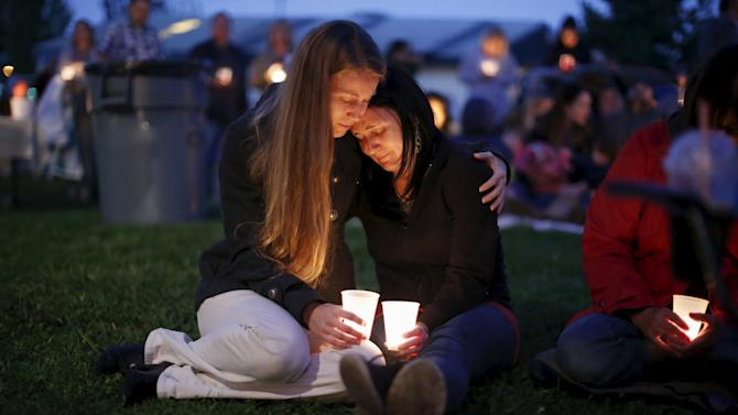Heidi Wickersham comforts her sister Gwendoline during a candlelight vigil for victims of the Umpqua Community College shooting in Winston