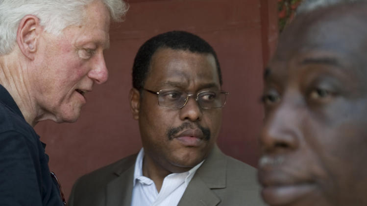 In this file photo taken Aug. 16, 2011, former U.S. President and UN special envoy to Haiti, Bill Clinton, left, speaks to Garry Conille, center, on the outskirts of Port-au-Prince, Haiti.  The long wait for Haiti to approve a prime minister ended Tuesday after the Senate voted in favor of Garry Conille to run the government. The 17-3 vote for Conille to serve as prime minister will enable Haitian President Michel Martelly to install a Cabinet .(AP Photo/Dieu Nalio Chery)