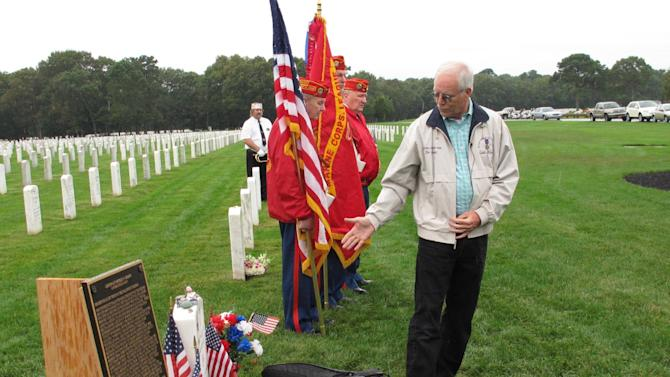 Daniel Murphy, the father of Navy SEAL Lt. Michael Murphy, notes some of the tributes left at the gravesite of his son at Calverton National Cemetery on Tuesday, Oct. 2, 2012. Murphy spoke at a memorial service attended by crew members of the USS Michael Murphy, a Navy destroyer named for the Medal of Honor winner that will be formally commissioned in New York City on Saturday, Oct. 6. (AP Photo/Frank Eltman)