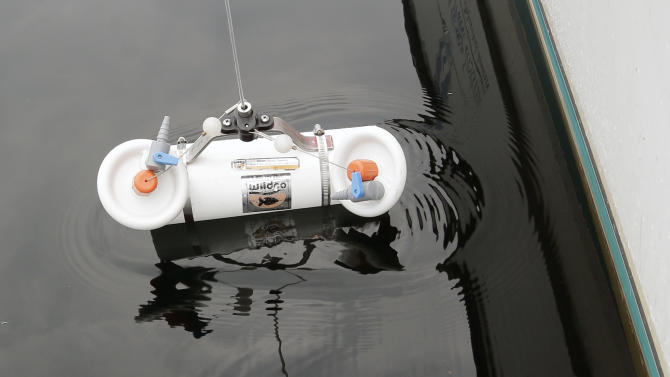 """Larry Eichler, a researcher scientist for Rensselaer Polytechnic Institute's Darrin Fresh Water Institute, lowers a sampling bottle into Lake George to collect water samples on Wednesday, June 26, 2013, in Bolton Landing, N.Y. An unprecedented project to turn New York's Lake George into the """"smartest lake in the world"""" is being launched to monitor the lake from its sun-dappled shores to its dark depths in hopes of keeping the Adirondack attraction pristine. (AP Photo/Mike Groll)"""