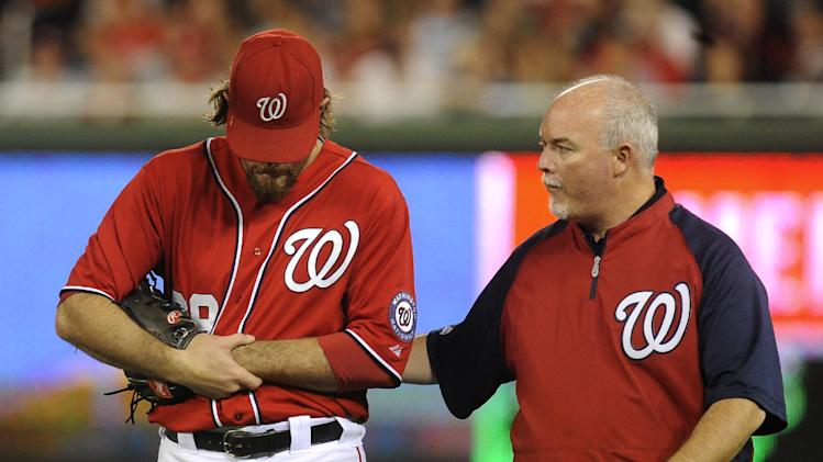 Washington Nationals' right fielder Jayson Werth holds his left wrist as he walks off the field with assistant athletic trainer Mike McGowan after a play on Philadelphia Phillies' Placido Polanco's fly ball in the sixth inning of their baseball game at Nationals Park, Sunday, May 6, 2012, in Washington. The Phillies defeated the Nationals 9-3. (AP Photo/Richard Lipski)