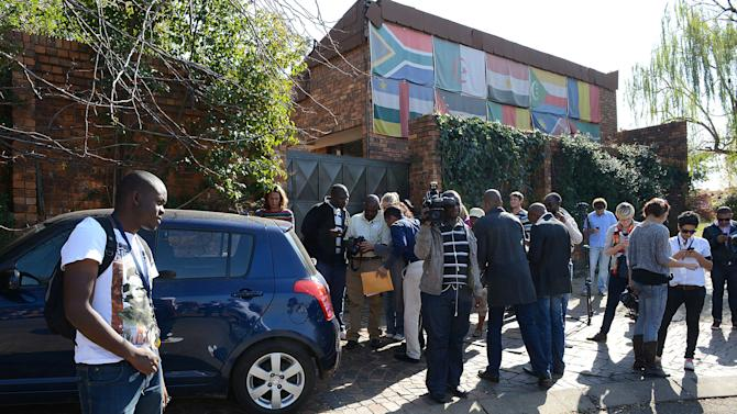 Press gather outside the Soweto, South African home of Winnie Madikizela-Mandela, former wife of former president Nelson Mandela, Tuesday, May 21, 2013.  A scheduled auction to sell items belonging to Madikizela-Mandela came and went without a single bid. Court sheriff John Maluleke and two other officials joined reporters gathered outside the gated home where some of her items were expected to be sold to cover an old debt she owes for school fees for her grand-niece, but were denied entry despite officials repeatedly banging on the gate. (AP Photo) SOUTH AFRICA OUT