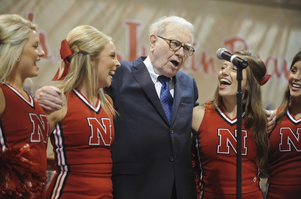 Warren Buffett, chairman and CEO of Berkshire Hathaway sings with University of Nebraska cheerleaders prior to the annual shareholders meeting in Omaha, Neb., Saturday, May 5, 2012. Berkshire Hathaway is holding it's annual shareholders meeting this weekend. (AP Photo/Dave Weaver)