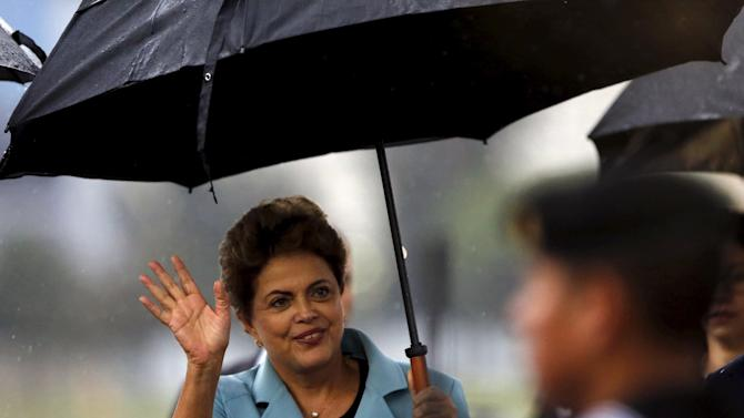 Brazilian President Dilma Rousseff waves to the media after her arrival at the presidential hangar in Mexico City