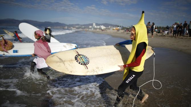 Competitors run into the Pacific Ocean during the 7th annual ZJ Boarding House Haunted Heats Halloween surf contest in Santa Monica