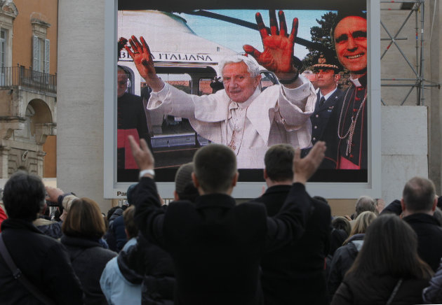 Faithful watch a giant screen showing Pope Benedict XVI  in St. Peter's Square, at the Vatican,Thursday, Feb. 28, 2013. The 85-year-old German Pope Benedict is stepping down on Thursday evening, the f