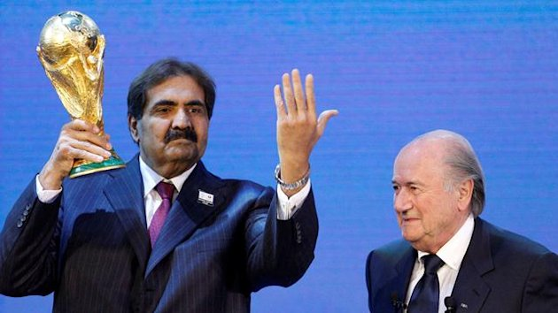 Qatar's Emir Sheikh Hamad bin Khalifa al Thani (L) holds up a copy of the World Cup he received from FIFA President Sepp Blatter