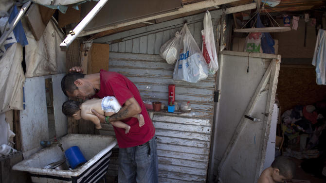 "Ricardo Gonzalez pours water on his head and also on of her 8-month old daughter Keyla at their home at San Pablo shanty town in Santiago, Chile, Wednesday, Jan. 23, 2013. At right is Gonzalez's son, Antonio, 3. European, Latin American and Caribbean leaders gathering for this weekend's economic summit will likely see only one side of Chile _ the polished, upscale country where tourists and investors stay in five-star hotels in a sparklingly clean financial district nicknamed ""Sanhattan,"" well away from Santiago's slums. (AP Photo/Victor R. Caivano)"