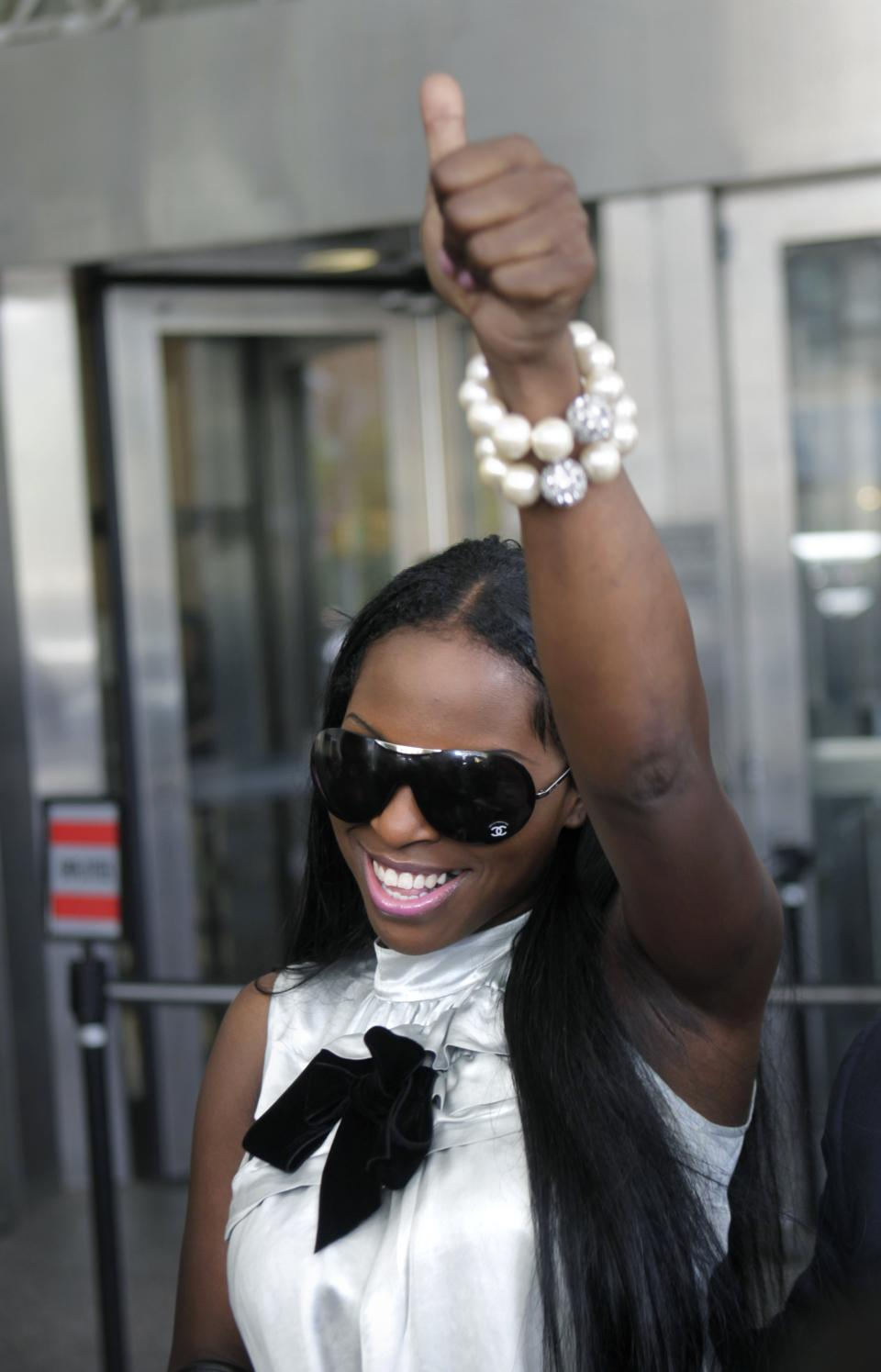 Inga Marchand, also known as Foxy Brown, gives a thumbs-up after leaving court in New York, Tuesday, July 12, 2011. Charges that rapper Foxy Brown violated a court order by mooning her neighbor have been dropped. (AP Photo/Seth Wenig)