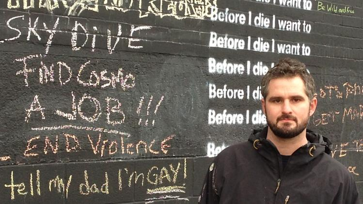 "In this Nov. 7, 2013 photo, Rick Destito poses near the ""Before I Die"" wall he painted on the former factory building he owns in Syracuse, N.Y. The inscription on the building invites passers-by to complete the sentence: ""Before I die, I want to..."" The phenomenon became global since artist Candy Chang created the first wall on an abandoned house in her New Orleans neighborhood in 2011. More than 400 walls have gone up in the United States as well as 60 other countries. (AP Photo/Carolyn Thompson)"