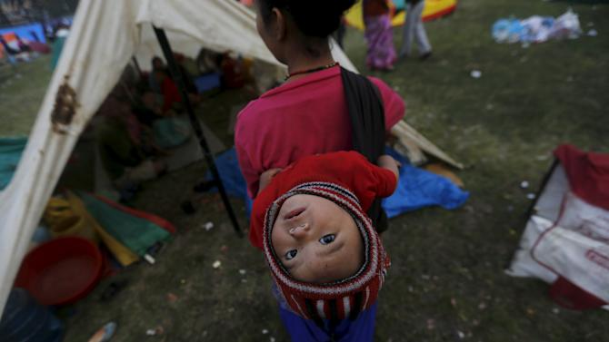 An earthquake victim carries her baby on her back as she stands outside her makeshift shelter on open ground in the early hours in Kathmandu