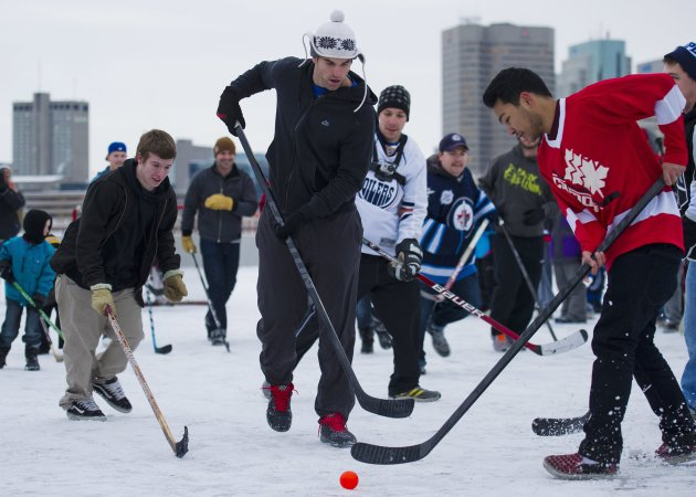 Winnipeg Jets captain Andrew Ladd, center, plays street hockey with hockey fans and a few fellow NHL players atop a parking garage at the Forks in Winnipeg, Manitoba, on Tuesday, Nov. 13, 2012. The lockout between the NHL and the players is in it&#39;s 59th day. (AP Photo/The Canadian Press, David Lipnowski)