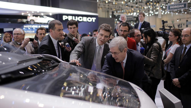 French Minister for Industrial Recovery Arnaud Montebourg, center, reacts as he speaks with PSA Peugeot Citroen Chief Executive Philippe Varin, right, during the first media day of the 83rd Geneva International Motor Show, Switzerland, Tuesday, March 5, 2013. The Motor Show will open its gates to the public from March 7 to 17.  (AP Photo/Laurent Cipriani)