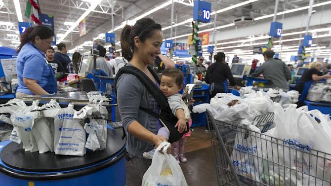 In this Wednesday, Nov. 22, 2012, photo, Eva Cevallos with her eleven-month daughter, Quinn, shop during the Thanksgiving Pre-Black Friday event at the Walmart Supercenter store in Rosemead, Calif. Wal-Mart Stores Inc. offered a weak business outlook Thursday, Feb. 21, 2013,  as new economic challenges for its low-income U.S. shoppers start to take a toll.  (AP Photo/Damian Dovarganes)