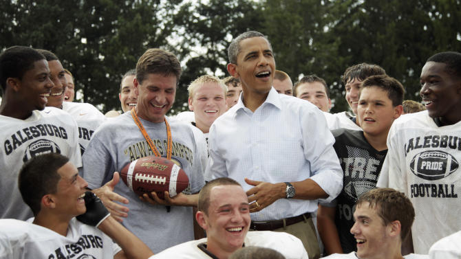 FILE - In this Aug. 17, 2011 file photo, President Barack Obama reacts to catching a football tossed to him as he visits the Galesburg High School football team in Galesburg, Ill., during a three-day economic bus tour. The president has developed a lasting tie to this small, economically bruised town with an empty refrigerator plant and a liberal arts college where he likes to roll-out big economy speeches. He is scheduled to give an economic speech at Knox College in Galesburg on Wednesday, July 24, 2013. (AP Photo/Carolyn Kaster, File)