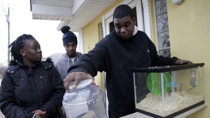 In this Nov. 1, 2012, photo, Gregory Labidou, right, tries to figure out what to do with his pet gerbils and tarantula after he was forced to evacuate his home because of damage from Superstorm Sandy in the Midland Beach section of Staten Island, New York. His aunt, Irmine Celestine, left, agreed to take the gerbils, but not the tarantula, until Labidou could find a more permanent place to stay. Superstorm Sandy drove New York and New Jersey residents from their homes, destroyed belongings and forced them to find shelter for themselves _ and for their pets, said owners, who recounted tales of a dog swimming through flooded streets and extra food left behind for a tarantula no one was willing to take in.  (AP Photo/Seth Wenig)