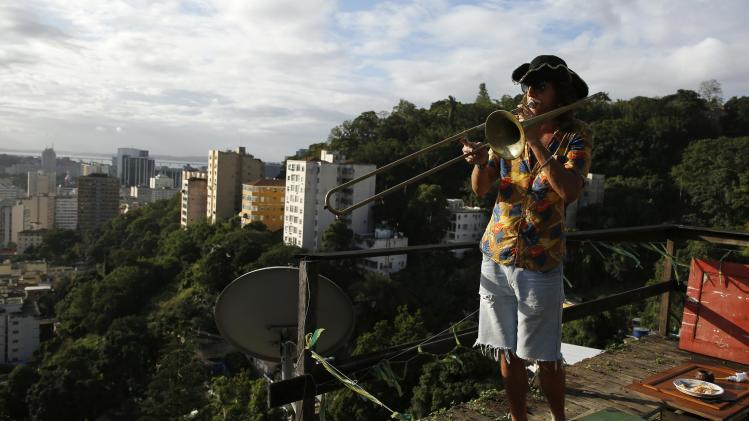 An Argentinian fan plays a trumpet on the terrace of a rented house in Rio de Janeiro