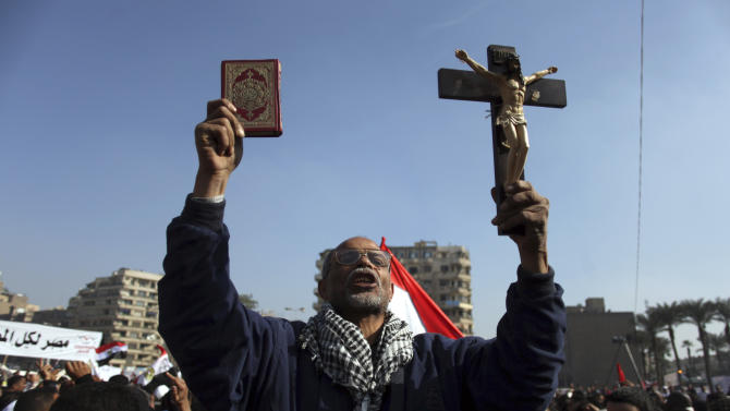 """An Egyptian protesters holds a cross and a Quran as he chants anti-Muslim Brotherhood slogans at an opposition rally in Tahrir Square, in Cairo, Egypt, Friday, Nov. 30, 2012. Egypt's opposition has called for a major rally Friday in Cairo's Tahrir Square, where some demonstrators have camped out in tents since last week to protest decrees that President Mohammed Morsi issued to grant himself sweeping powers. Hundreds gathered in the plaza for traditional Friday prayers, then broke into chants of """"The people want to bring down the regime!"""" — echoing the refrain of the Arab Spring revolts, but this time against a democratically elected leader. Other cities around Egypt braced for similar protests. (AP Photo/Khalil Hamra)"""
