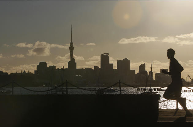A jogger runs along the waterfront of Okahu Bay as the sun begins to set behind the main business district in Auckland, New Zealand, Monday, Sept. 26, 2011. The tower is 328 meters high (1,076 feet),