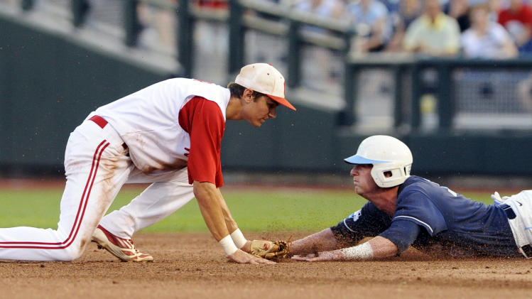 North Carolina's Colin Moran, right, slides safely to second base as North Carolina State shortstop Trea Turner looks on following a throwing error during the fourth inning of an NCAA College World Series elimination baseball game in Omaha, Neb., Thursday, June 20, 2013. (AP Photo/Eric Francis)