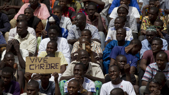 A man holds up a sign reading 'Long live the CNRDRE,' the acronym by which the ruling military junta is known, during a rally in support that was attended by roughly one thousand people in a stadium with a capacity of 50,000, in Bamako, Mali Saturday, March 31, 2012. The March 26 stadium is named in commemoration of the date in 1991 when dictator Moussa Traore was overthrown, paving the way for establishment of a democracy which lasted 21 years until mutinous soldiers took power in a coup nine days ago. (AP Photo/Rebecca Blackwell)