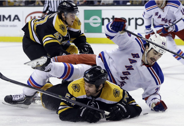 New York Rangers center Brian Boyle (22) goes down to the ice as he chases the puck against Boston Bruins defensemen Adam McQuaid (54) and Torey Krug (47) during the first period in Game 2 of the NHL 