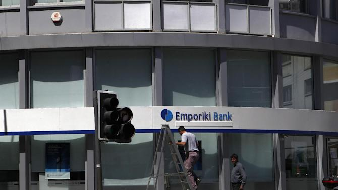 """A worker on a ladder works for a branch of Greek bank Emporiki in central capital Nicosia, Cyprus, Friday, April 12, 2013. President Nicos Anastasiades said that he will dispatch letters to EU Commission President Jose Manuel Barosso and EU Council chief Herman Van Rompuy telling them of the """"need for a change of EU policy"""" toward Cyprus by offering additional assistance. (AP Photo/Petros Karadjias)"""