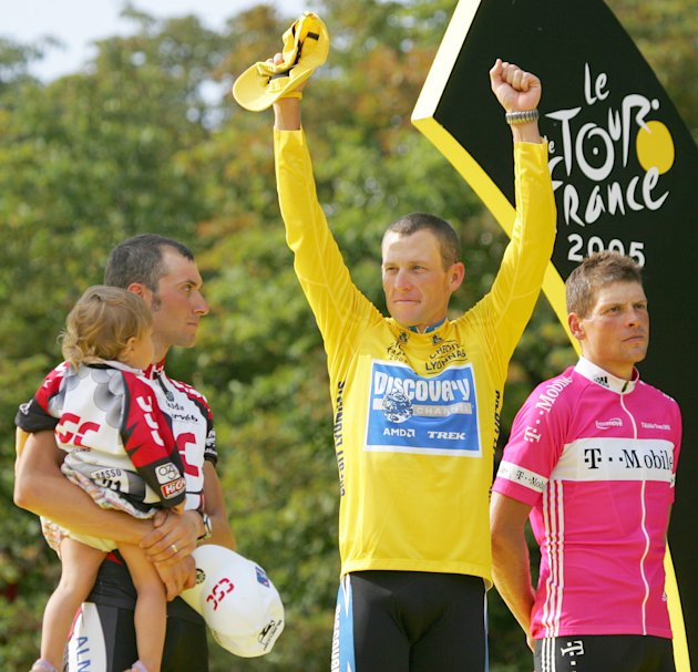 In this July 24, 2005 file photo,  Lance Armstrong gestures from the podium after winning his seventh straight Tour de France cycling race, as second-placed Ivan Basso of Italy, left, and third-placed