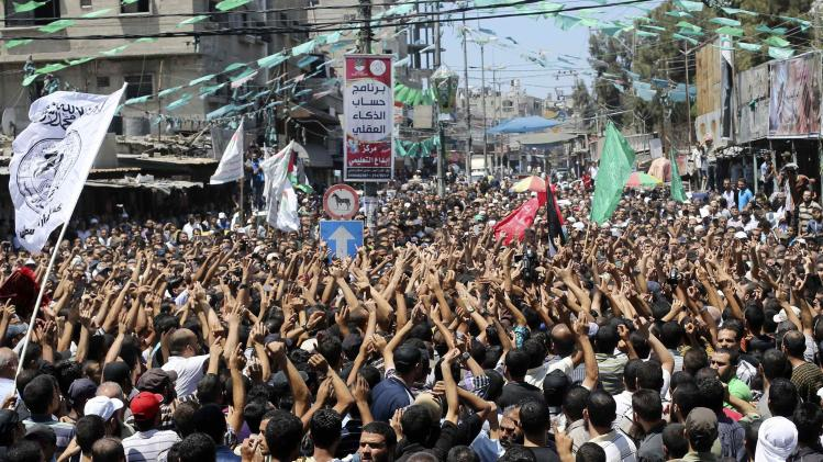 Palestinians carry the bodies of three senior Hamas commanders during their funeral in Rafah