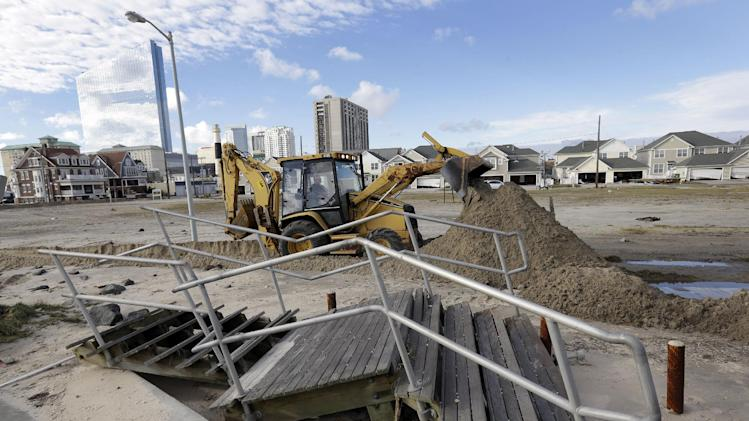 A worker uses a backhoe to clear sand and debris that was carried onshore by surge from superstorm Sandy in Atlantic City, N.J., Wednesday, Oct. 31, 2012. Sandy, the storm that made landfall Monday, caused multiple fatalities, halted mass transit and cut power to more than 6 million homes and businesses. (AP Photo/Patrick Semansky)
