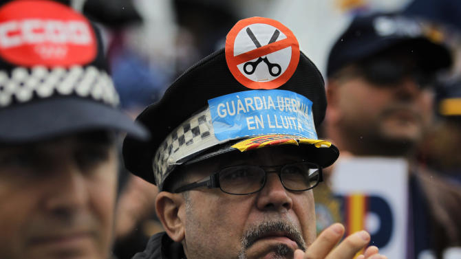 """A police officer wears a hat with a banner reading, """"Urban guards in conflict"""" during a protest  against government's austerity measures and the elimination of their Christmas bonus pay, one of 14 paychecks that most Spanish civil servants get each year, in Madrid, Spain, Saturday, Nov. 17, 2012. (AP Photo/Andres Kudacki)"""