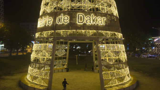 """In this Wednesday, Dec. 12, 2012 photo, a child runs through a giant cone of lights, reading """"Mayor of Dakar,"""" in central Dakar, Senegal. As Christmas approaches in mostly Muslim Senegal, vendors ply the streets selling tinsel, artificial trees, and inflatable Santas, and the main boulevards are all aglow in holiday lights. Senegal, a moderate country along Africa's western coast, has long been a place where Christians and Muslims coexist peacefully and share in each other's holidays. (AP Photo/Rebecca Blackwell)"""