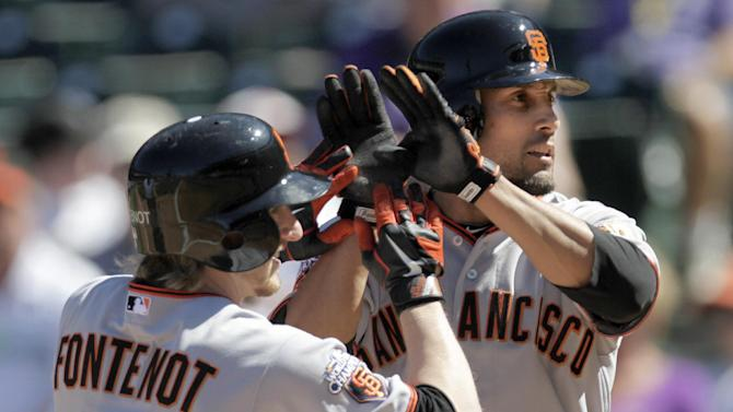 San Francisco Giants' Mike Fontenot (14) and Andres Torres (56) meet at home plate after Fontenot  hit a two-run homer against the Colorado Rockies during the first inning of a baseball game Sunday, Sept. 18, 2011 in Denver. (AP Photo/Barry Gutierrez)