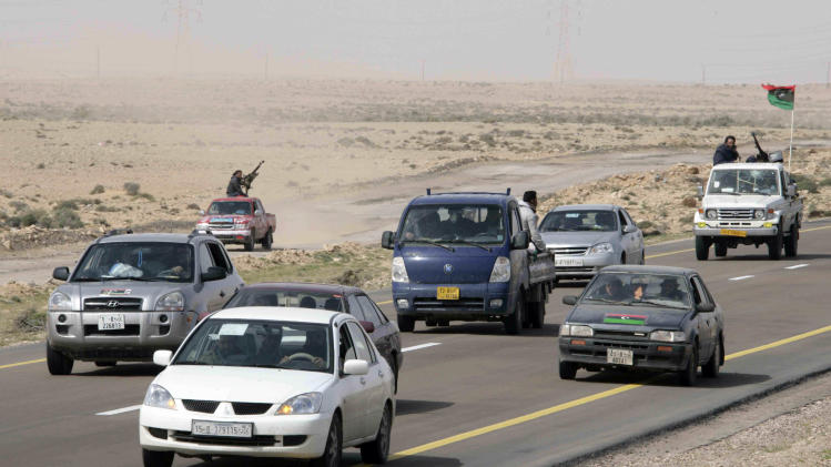 Libyan rebels ride in a convoy leaving Ras Lanouf, Libya, Wednesday, March 30, 2011. Moammar Gadhafi's ground forces recaptured a strategic oil town Wednesday and were close to taking a second, making new inroads in beating back a rebel advance toward the capital Tripoli. (AP Photo)