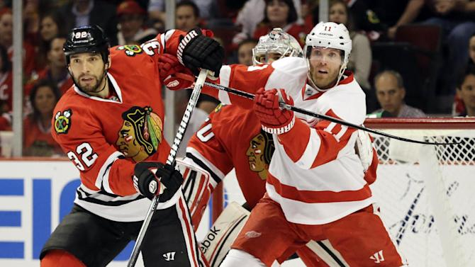 Detroit Red Wings' Daniel Cleary, right, and Chicago Blackhawks' Michal Rozsival battle as they wait for the puck during the first period of Game 1 of an NHL hockey playoffs Western Conference semifinal in Chicago, Wednesday, May 15, 2013. (AP Photo/Nam Y. Huh)