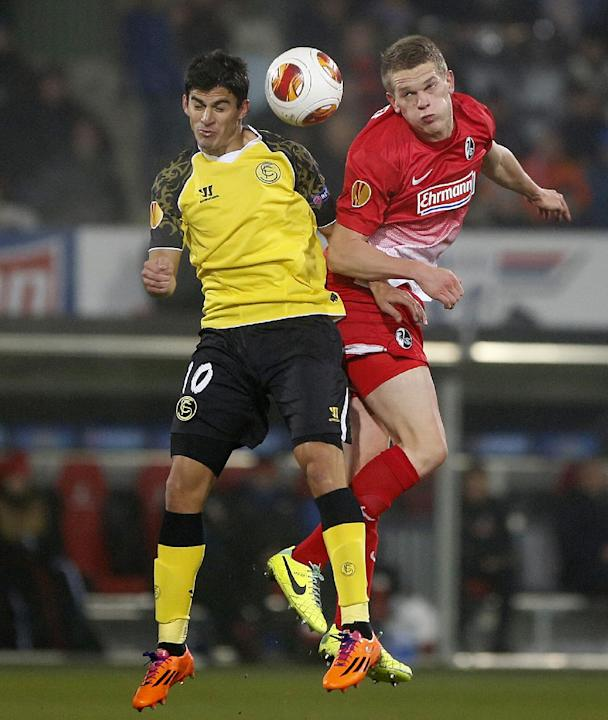 Freiburg's Matthias Ginter, right, and Sevilla's Diego Perotti jump for the ball during a Group H Europa League match between SC Freiburg and Sevilla FC in Freiburg, Germany, Thursday, Dec.12,