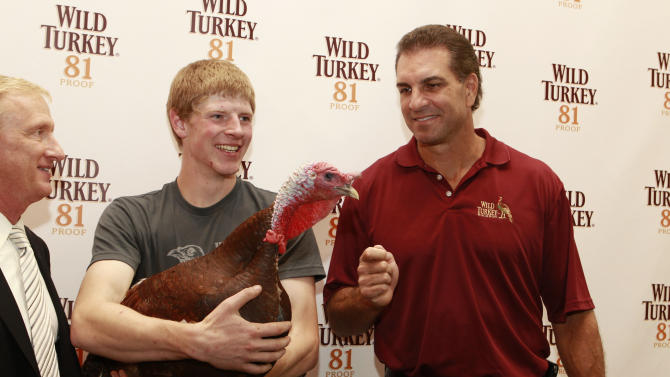 IMAGE DISTRIBUTED FOR WILD TURKEY - Sports announcer Jimmy Lennon Jr, Turkey handler Robert Rastly and Football legend Vinny Testaverde gives a few last minute pointers to football picking turkey Jimmy Junior  at the Wild Turkey Triple Barrel Challenge, on Tuesday, Nov. 20, 2012 in New York. (Photo by Mark Von Holden/Invision for Wild Turkey/AP Images)