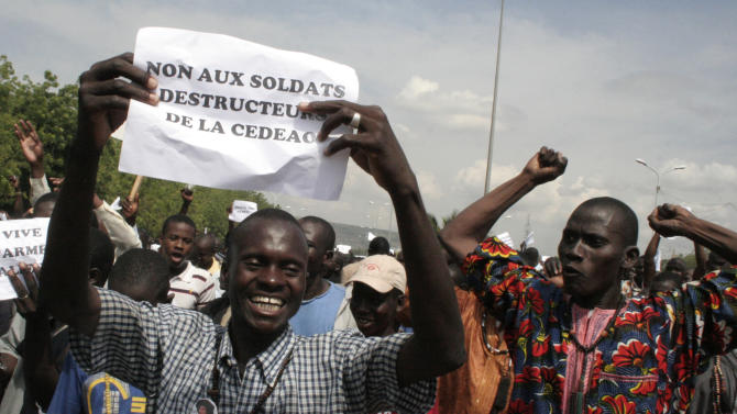 """FILE - A Thursday, Oct. 18, 2012 photo from files showing a man carrying a sign reading """"No to the destructive soldiers of ECOWAS"""" as Malians opposed to a military intervention to retake Mali's Islamist-controlled north march in the streets of the capital, Bamako, Mali. Two land-locked, desperately poor African countries many Americans would struggle to find on a map are both gripped by rebellions in the north that have left huge chunks of both nations outside of government control. So why are neighbors rushing troops into Central African Republic after only a few weeks, while Mali is still awaiting military help from its region nearly one year after its political chaos began? (AP Photo/Harouna Traore, File)"""